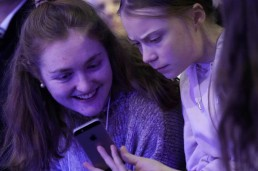 Swedish climate change activist Greta Thunberg and Swiss activist Loukina Tille look at a phone as they attend a session at the 50th World Economic Forum (WEF) annual meeting in Davos, Switzerland, January 21, 2020. REUTERS/Denis Balibouse
