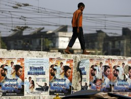 A child living on the street walks on a wall displaying publicity posters of Golden Globe award-winning film