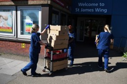 Nurses and staff carry food delivered by volunteers outside Guy's and St Thomas' Hospital as the spread of the coronavirus disease (COVID-19) continues, in London, Britain, March 23, 2020. REUTERS/Dylan Martinez