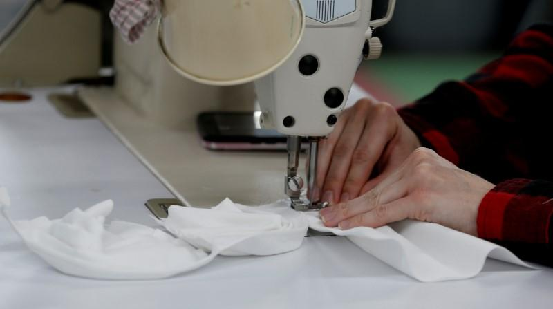 "Elise Thompson sews hospital masks as the spread of coronavirus disease (COVID-19) continues, on day one of turning the ""Detroit Sewn"" facility into a production facility for hospital masks, in Pontiac, Michigan, U.S. March 23, 2020. REUTERS/Rebecca Cook"