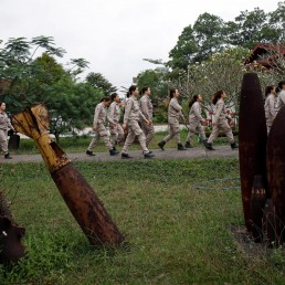 Members of all-female landmines clearance team walk past the shells of U.S. military bombs used during Vietnam War, at a bombs and landmines exhibition in Quang Tri province, Vietnam March 4, 2020. Picture taken March 4, 2020. REUTERS/Kham