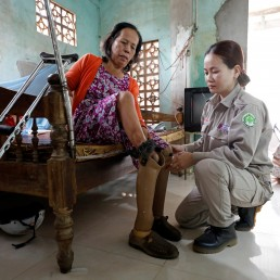 Hoang Thi Hoa, who lost both legs and an arm due to unexploded ordnance (UXO) during the Vietnam War, is assisted by her daughter Nguyen Thi Ha Lan, a member of all-female landmines clearance team, at their house in Quang Tri province, Vietnam March 4, 2020. Picture taken March 4, 2020. REUTERS/Kham