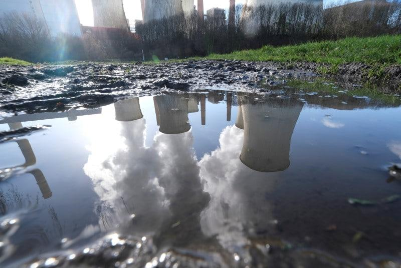 The lignite power plant complex of German energy supplier and utility RWE is reflected in a puddle in Neurath, north-west of Cologne, Germany, February 5, 2020. REUTERS/Wolfgang Rattay