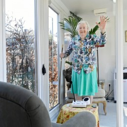 A woman gestures at a care facility for elderly people with dementia, in a glass house that is made especially against loneliness caused by the visit ban due to the coronavirus disease (COVID-19) outbreak in Wassenaar, Netherlands, April 9, 2020. REUTERS/Piroschka van de Wouw