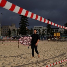 A man walks to the sea as Bondi Beach reopens to surfers and swimmers after it was closed to curb the spread of the coronavirus disease (COVID-19), with strict social distancing measures remaining in place, in Sydney, Australia, April 28, 2020. REUTERS/Loren Elliott