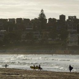 Surfers walk as Bondi Beach reopens to surfers and swimmers after it was closed to curb the spread of the coronavirus disease (COVID-19), with strict social distancing measures remaining in place, in Sydney, Australia, April 28, 2020. REUTERS/Loren Elliott