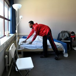 A homeless man makes the bed in his room in the old Overmaze prison as the existing shelter of the Salvation Army is closed due to the spread of coronavirus disease (COVID-19) in Maastricht, Netherlands, April 16, 2020. REUTERS/Piroschka van de Wouw