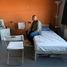 A homeless man sits in his room in the old Overmaze prison as the existing shelter of the Salvation Army is closed due to the spread of coronavirus disease (COVID-19) in Maastricht, Netherlands, April 16, 2020. REUTERS/Piroschka van de Wouw