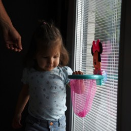 Macie Salinas looks out the window as her father, Tim, reaches to grab her hand amid a coronavirus disease (COVID-19) outbreak in San Antonio, Texas, U.S., May 7, 2020. REUTERS/Callaghan O'Hare
