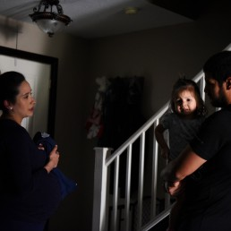Pregnant nurse Samantha Salinas waits to greet her daughter, Macie, and her husband, Tim, until after she changes the clothes she wore to her shift at the hospital amid a coronavirus disease (COVID-19) outbreak in San Antonio, Texas, U.S., May 7, 2020. REUTERS/Callaghan O'Hare