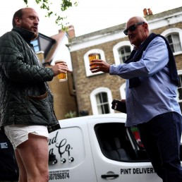 Customers drink freshly poured pints of beer from the Forest Road Brewing Co pub on wheels vehicle during its delivery round in Hackney, as the coronavirus disease (COVID-19) spread continues in London, Britain, May 12, 2020. REUTERS/Hannah McKay