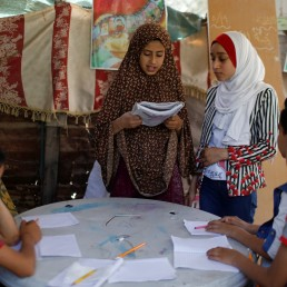 A girl reads out a text as Palestinian student Fajr Hmaid, 13, teaches her neighbours' children an Arabic language lesson as schools are shut due to the coronavirus disease (COVID-19) restrictions, at Hmaid's family house in Gaza, May 19, 2020. REUTERS/Mohammed Salem