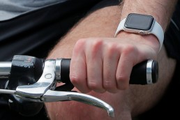 A bicyclist wearing a smart watch, which Stanford professor Michael Snyder suggests might be used to help in detection early COVID-19 infection, rides in Cambridge, Massachusetts, U.S., July 23, 2020. REUTERS/Brian Snyder