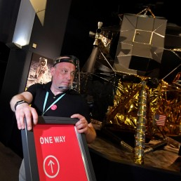Jon Kaddish, Visitor Experience Operations Manager, holds social distancing signage near a replica of the Apollo 11 Lunar Module, ahead of the reopening of the Science Museum, after lockdown restrictions were eased following the outbreak of the coronavirus disease (COVID-19), London, Britain, August 10, 2020. REUTERS/Toby Melville